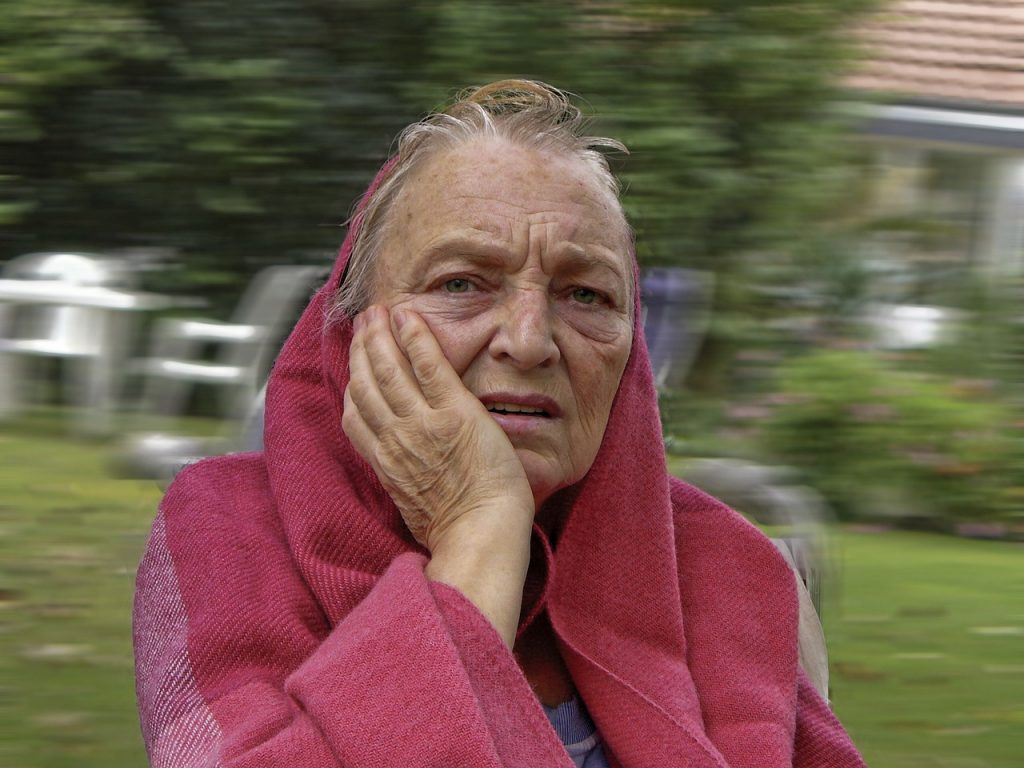 Older woman holding face